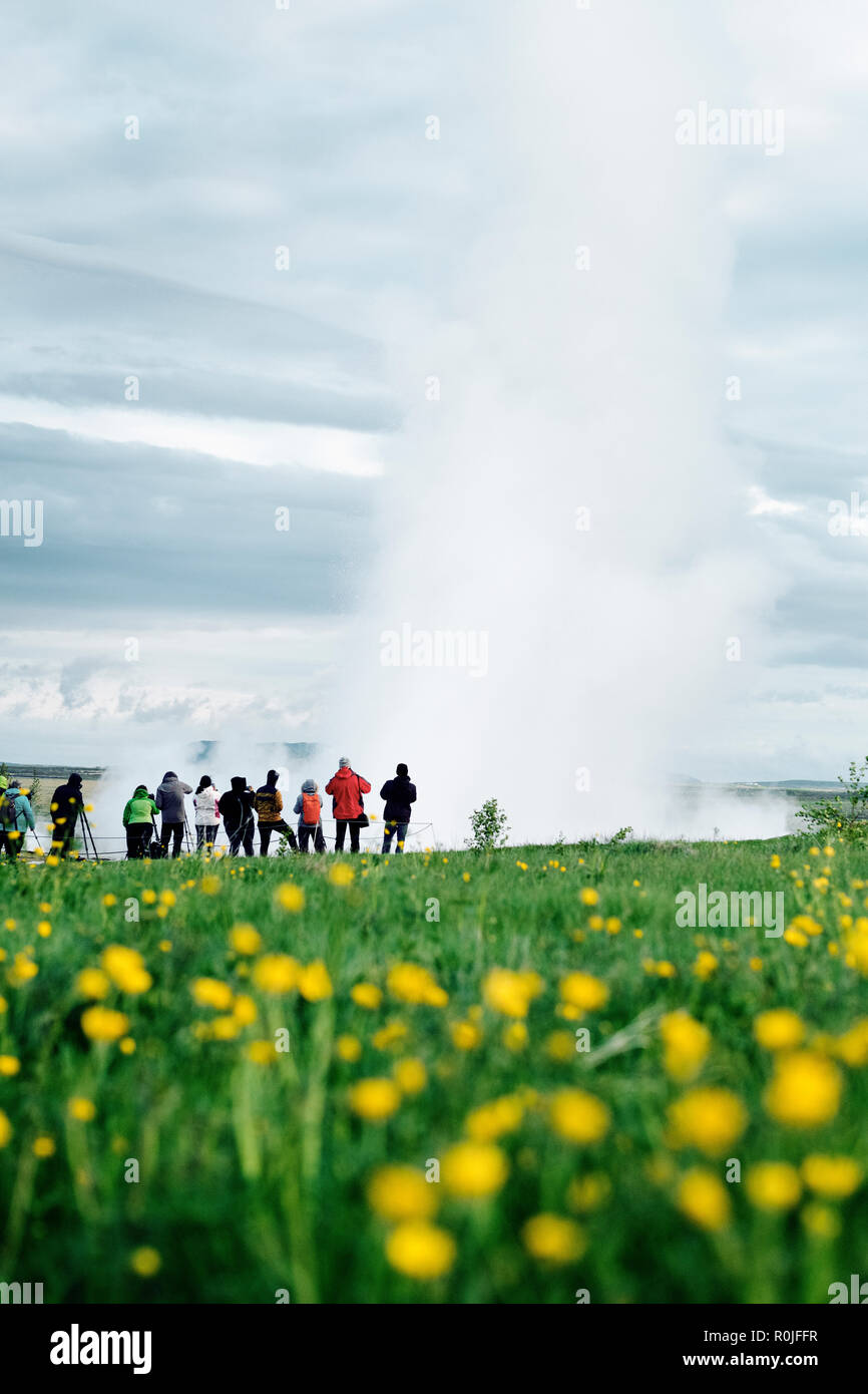 Tourists watching Strokkur geysir erupt in the popular destination of the geothermal hot springs in the Haukadalur Valley, south-west Iceland. - Stock Image