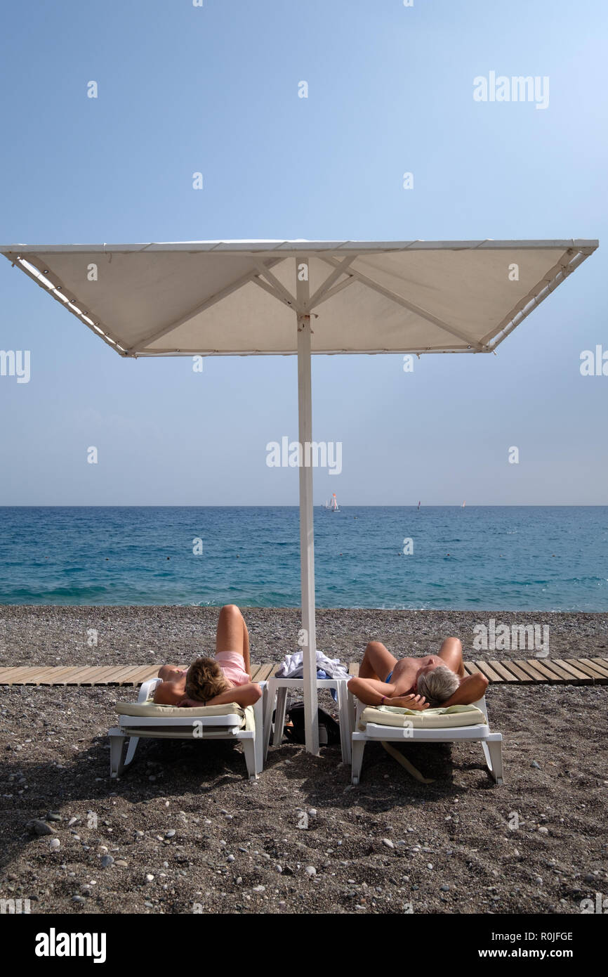 Two people sunbathing at the beach - Stock Image