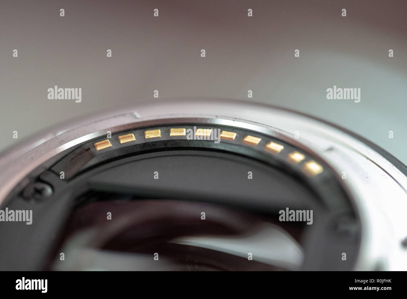 Gold contacts on the back of a camera lens - Stock Image