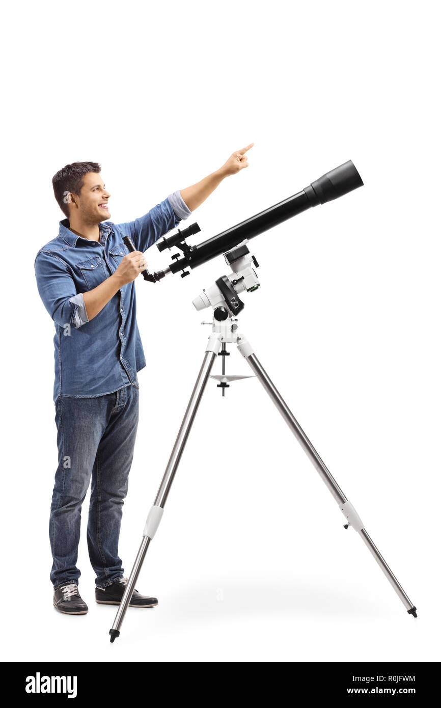 Full length shot a man standing next to a telescope and pointing up isolated on white background - Stock Image