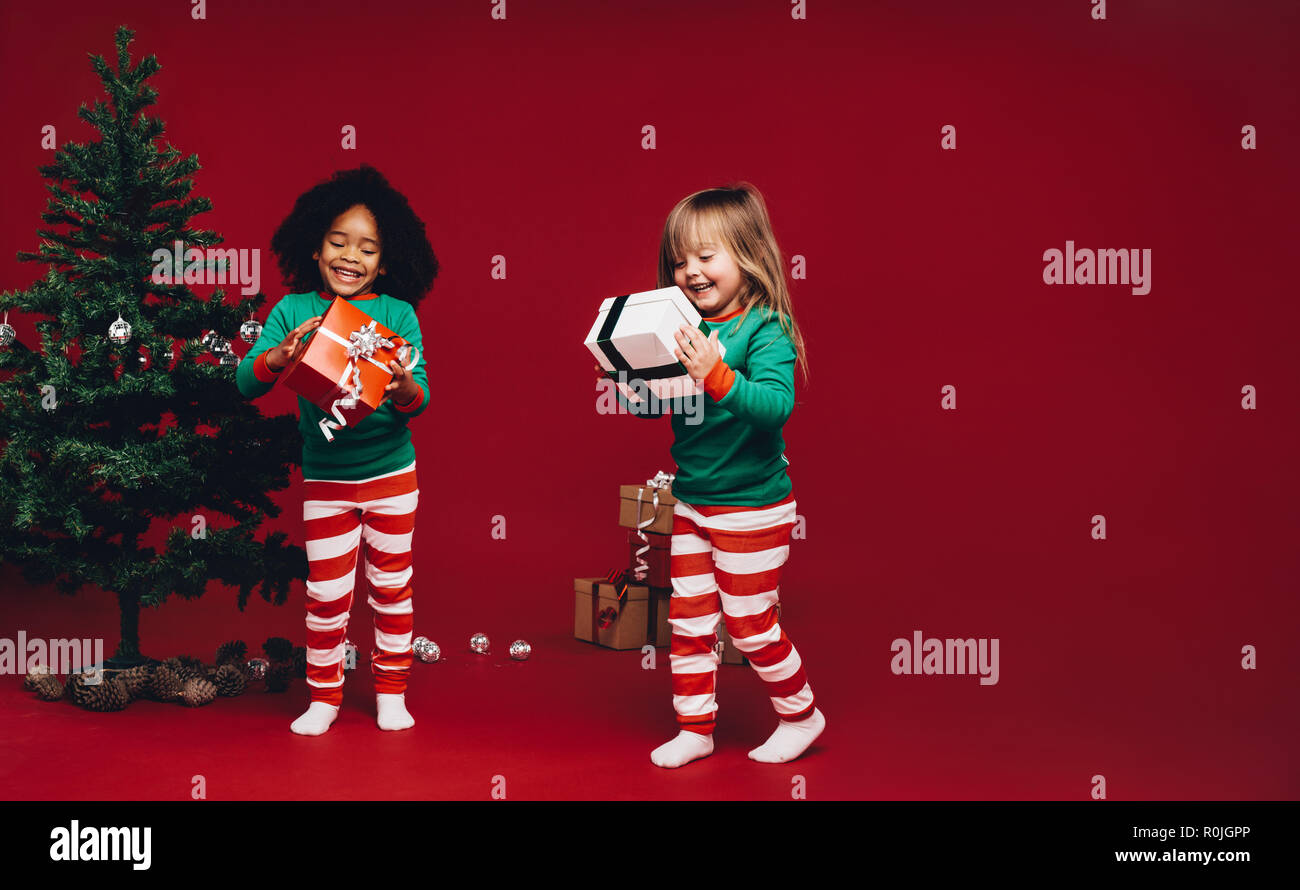 Two Little Girls Standing Beside A Christmas Tree Looking At Their Gift Boxes Happy Little Kids With Their Christmas Gifts Stock Photo Alamy