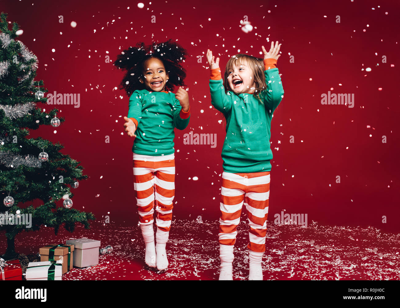 Little Girls In Christmas Costume Having Fun And Jumping Beside A Decorated Christmas Tree Two Kids Playing With Falling Artificial Snow Flakes Near Stock Photo Alamy