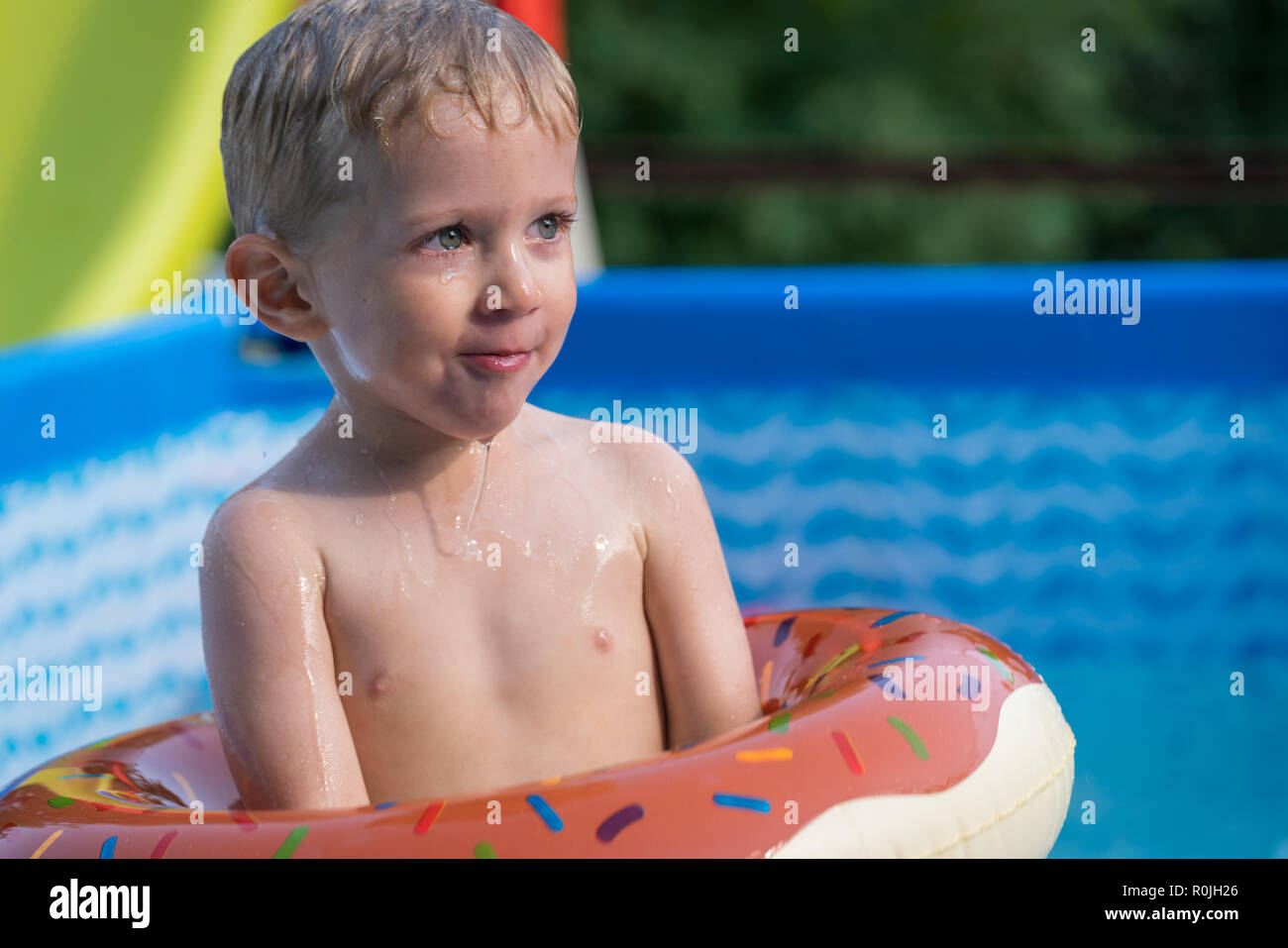 Happy little boy playing with colorful inflatable ring in outdoor swimming pool on hot summer day. Kids learn to swim. Child water toys. Stock Photo