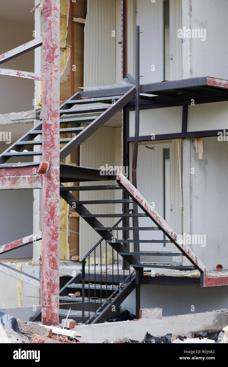Metallic staircase in front of partially demolished house. - Stock Image