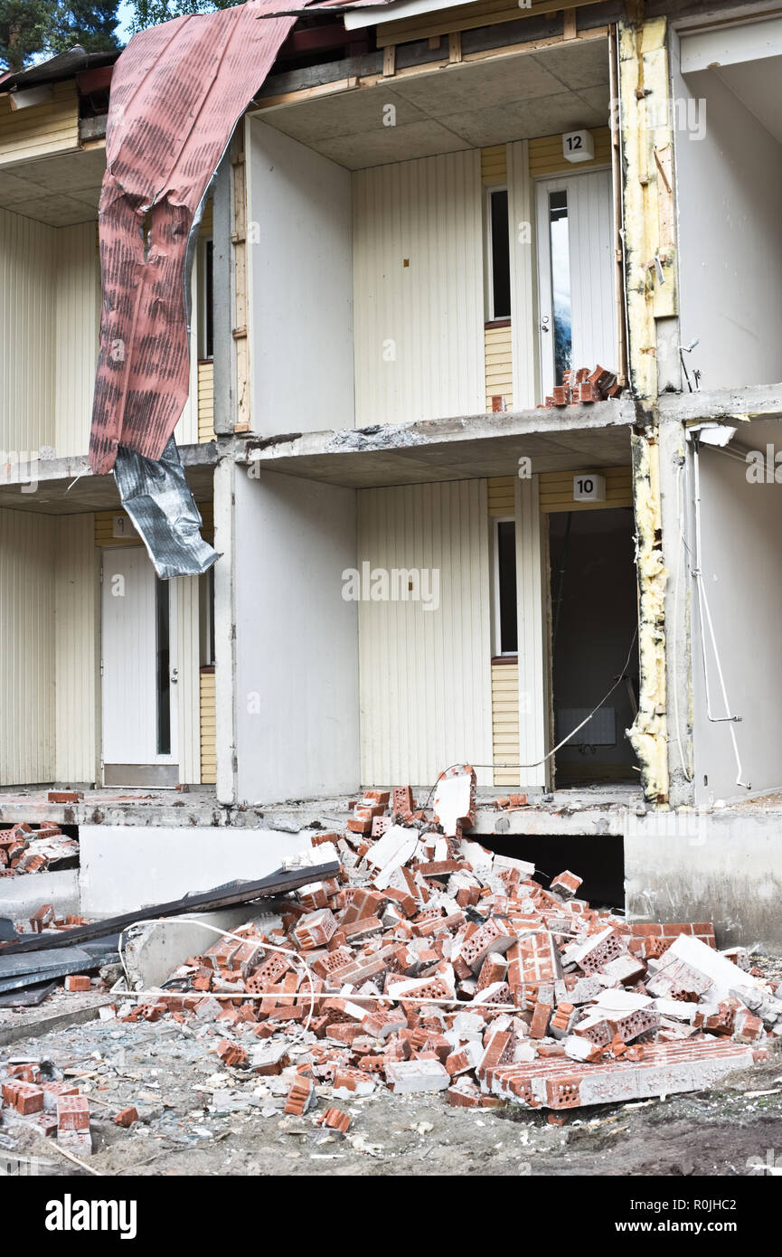 Pile of bricks in front of partially demolished house. - Stock Image