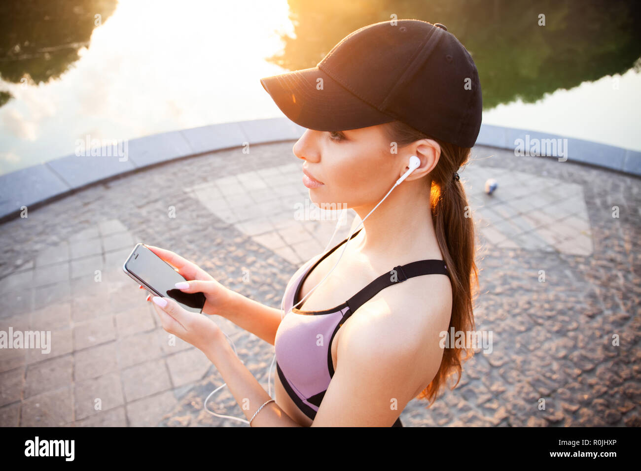 Tired fitness woman sweating taking a break listening to music on phone after difficult training. Young woman listening to music with earphones on smart phone app for fitness motivation. - Stock Image