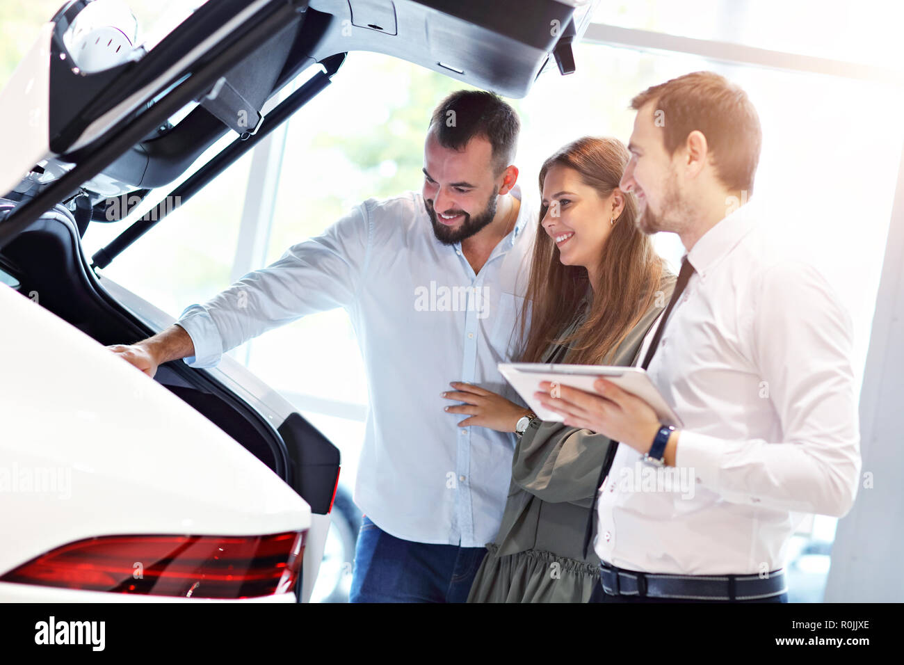 Confident young salesman explaining car features to the young attractive owners - Stock Image