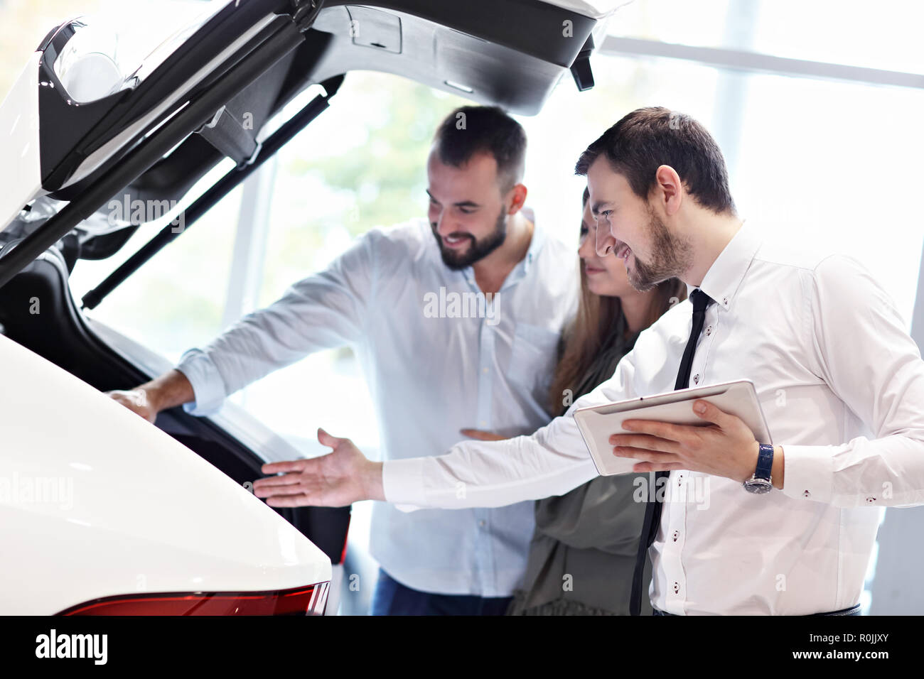 Confident young salesman explaining car features to the young attractive owners Stock Photo
