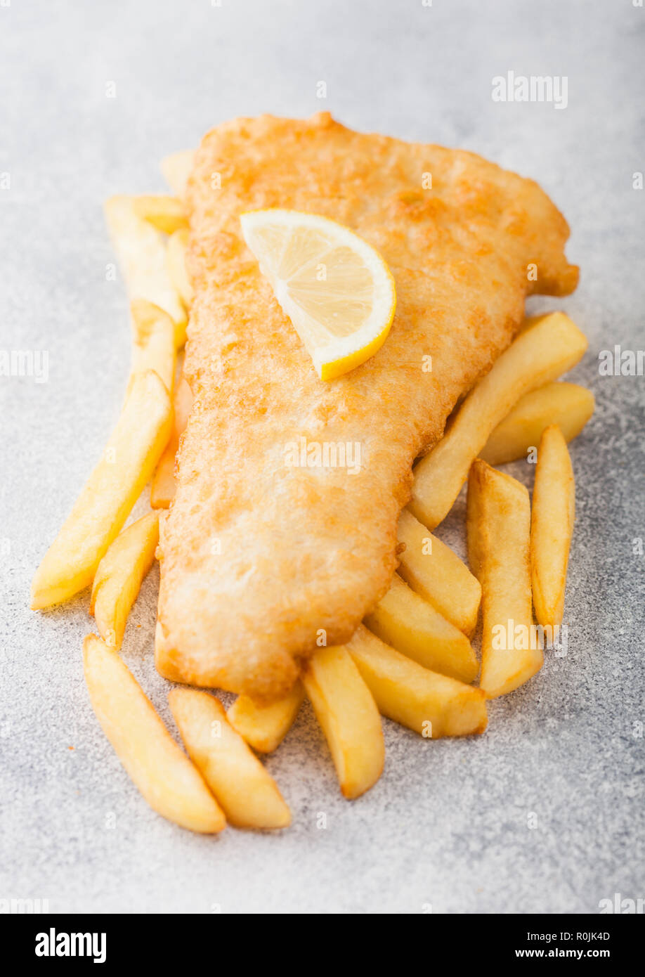 Traditional British Fish and Chips with lemon slice on white stone background. Stock Photo