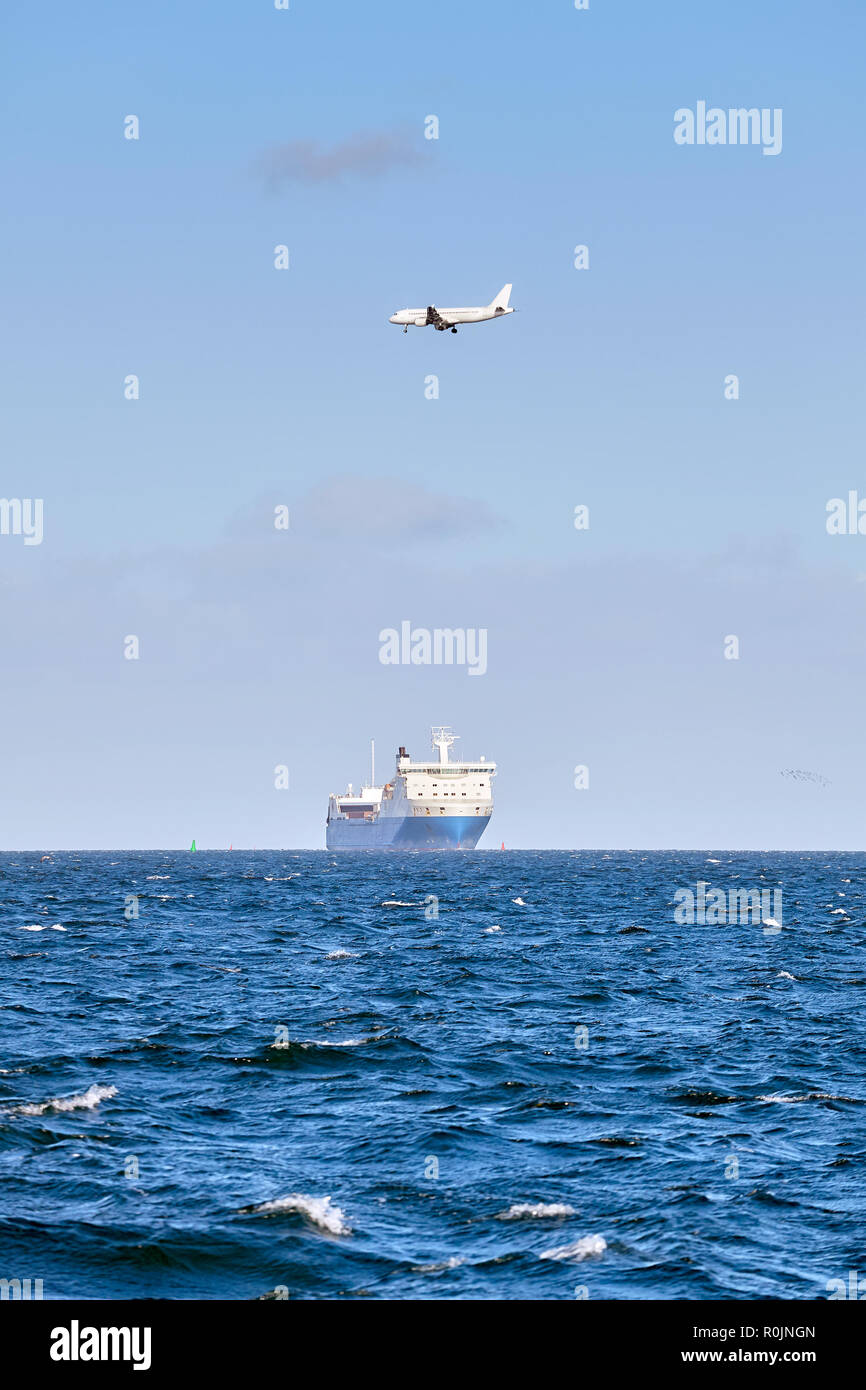 Airplane flying above a cruising ship, transport and logistics concept, authentic picture. - Stock Image