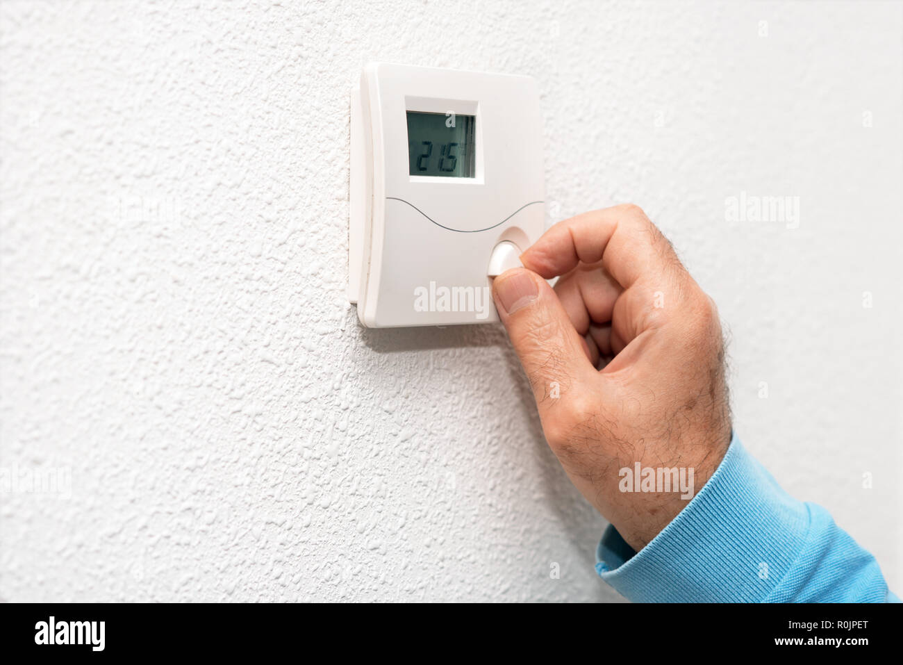 Man hand adjusting thermostat at home. Celsius temperature scale. - Stock Image