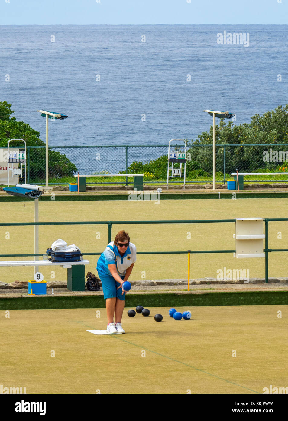 Woman playing lawn bowls at Clovelly Bowling and Recreation Club Sydney NSW Australia. - Stock Image