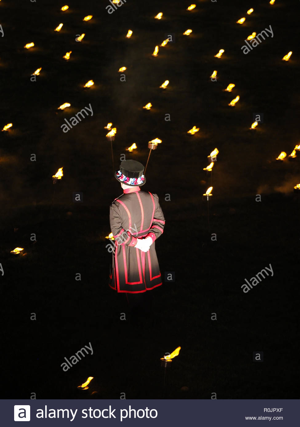 View of a Beefeater standing guard amid the thousands of torches lit to remember the WW1 Armistice Centenary at the Tower of London November 2018 Stock Photo