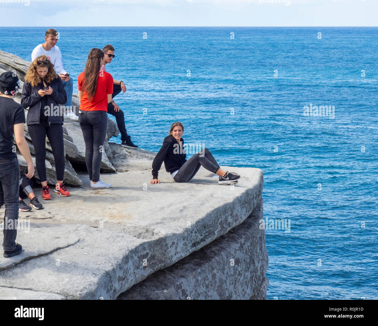 Group of young adults sitting on the edge of Sandstone rocks on the Bondi to Coogee Walk and Pacific Ocean Sydney NSW Australia. - Stock Image