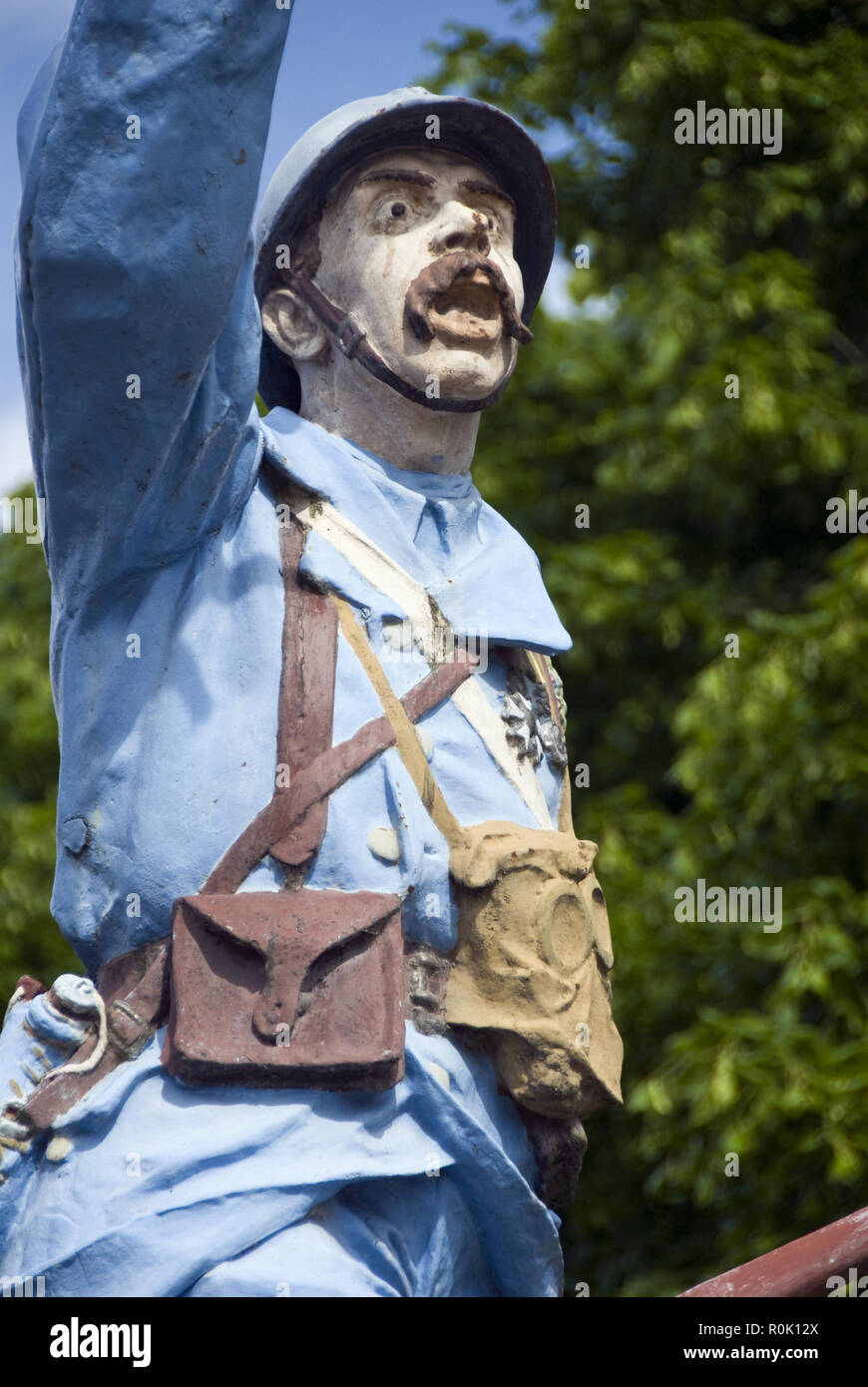 A colorfully painted statue of a WW I French soldier stands as a war monument in the center of La Commune de Cappy, in the Somme, France. - Stock Image