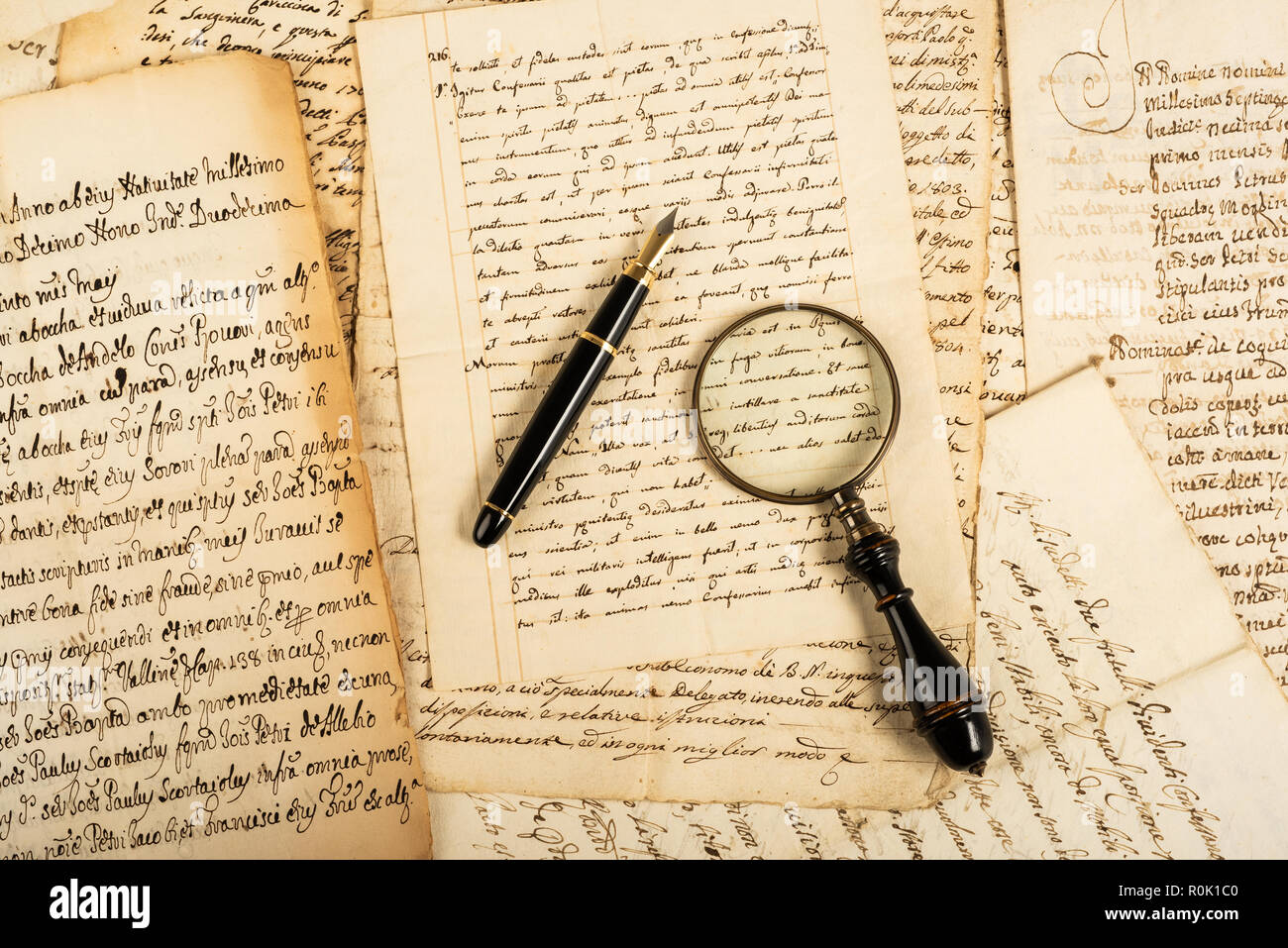 Fountain pen and magnifying glass with letters - Stock Image