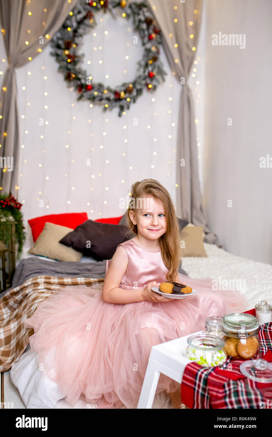 Pretty Little Girl 4 Years Old In A Pink Dress Child The Christmas Room With Bed Eating Candy Chocolate Cookies And Drinking Tea Feeding Ted Stock Photo Alamy