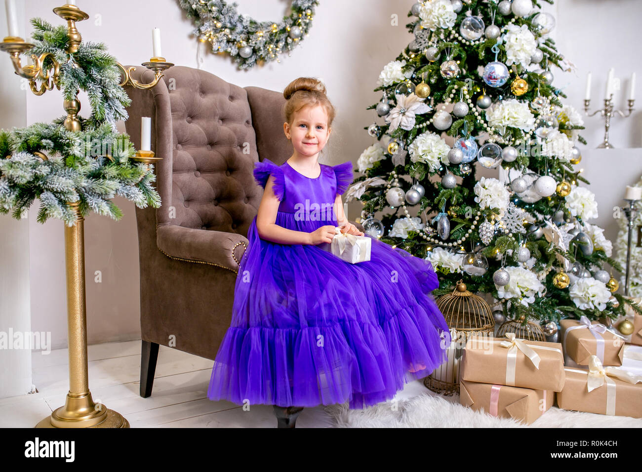 Pretty little girl 4 years old in a blue dress. Baby in Christmas ...
