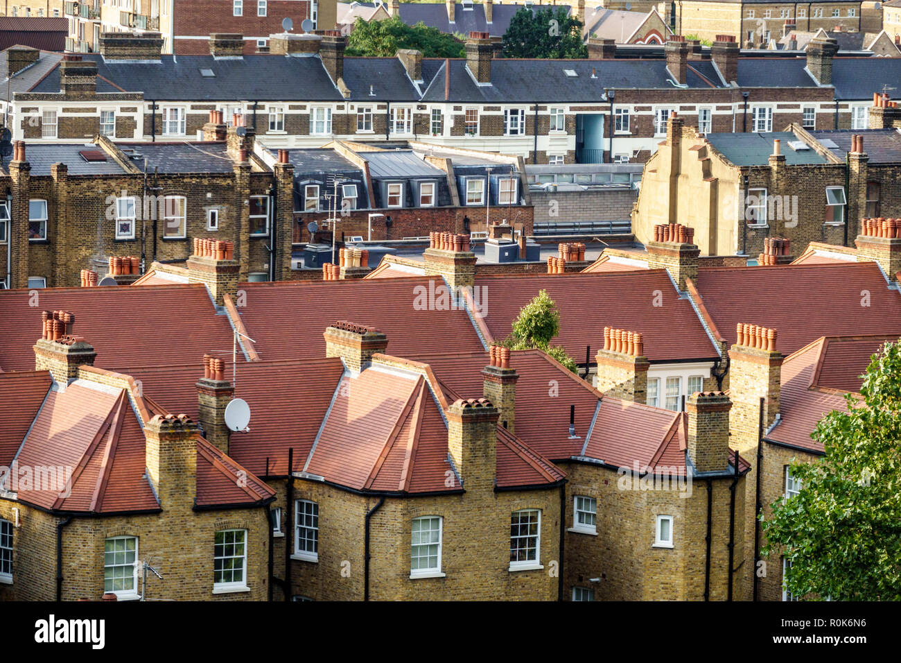 London England United Kingdom Great Britain Lambeth South Bank terraced row houses rooftops identical mirror image houses townhomes chimneys tiled roo - Stock Image