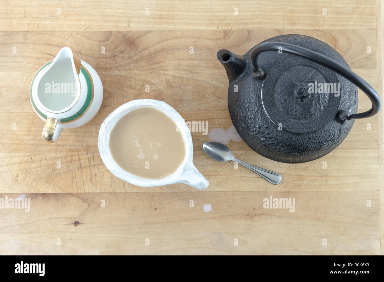Top view of Black cast iron tea pot with warm cup of tea and pitcher of cream and spoon on a wooden table or tray. - Stock Image