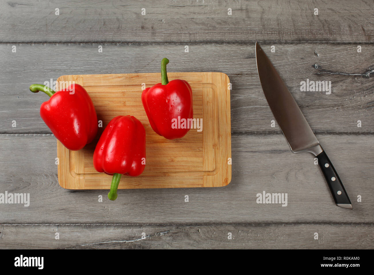 Tabletop view, three red bell peppers, sprayed with drops of water, ready to be cut on chopping board, with chef knife at side. - Stock Image
