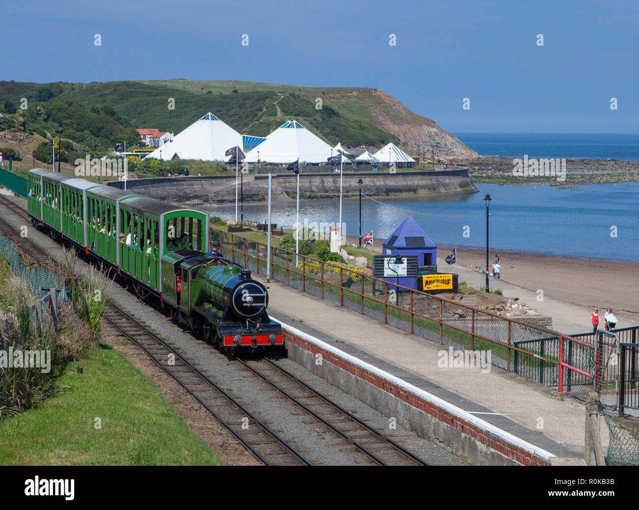 A miniature steam train pulls into a station on the North Bay Railway visitor attraction in Scarborough, North Yorkshire - Stock Image