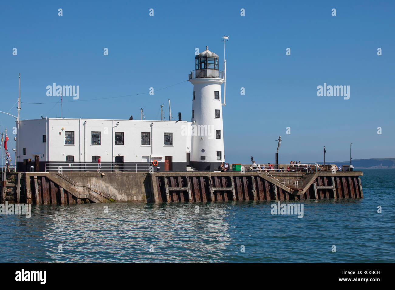 The white painted lighthouse on Scarborough Vincent Pier (West pier) on a sunny, blue sky summer day - Stock Image