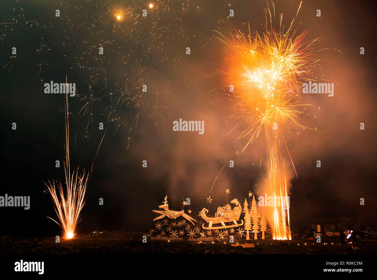 Fireworks next to a unlit bonfire in the shape of a Christmas sleigh filled with presents during the Skinningrove bonfire celebrations in North Yorkshire. - Stock Image