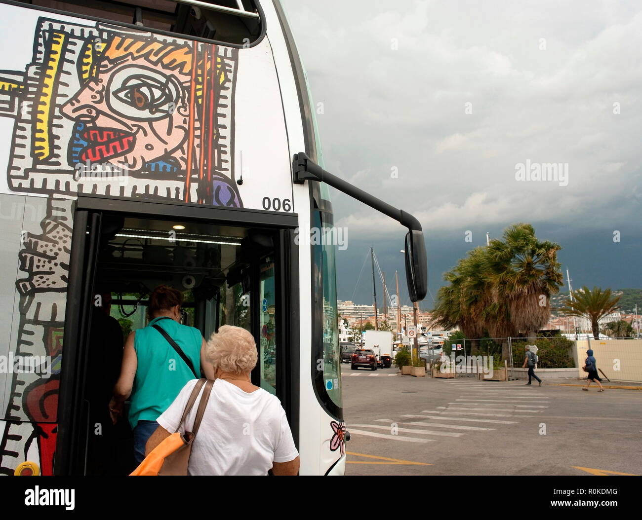AJAXNETPHOTO. 2018. CANNES, FRANCE. - COTE D'AZUR RESORT - PASSENGERS BOARDING THE PALM BEACH BUS AT THE OLD PORT NEAR LE SUQUET WITH A STORM BREWING OVER THE MOUNTAINS BEHIND THE TOWN. PHOTO:JONATHAN EASTLAND/AJAX REF:GXR180310_663 - Stock Image