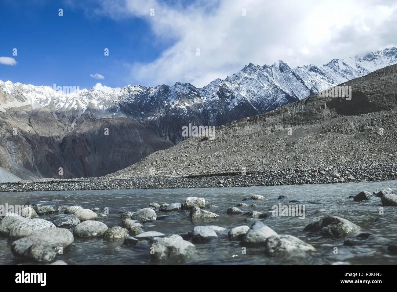 Flowing water stream among snow capped mountains in Karakoram range. - Stock Image
