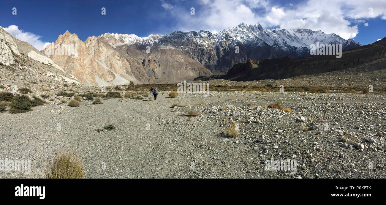 Trekking trail in Passu show drought landform, snow capped mountains in Karakoram range, grass and succulent plants along the way. - Stock Image