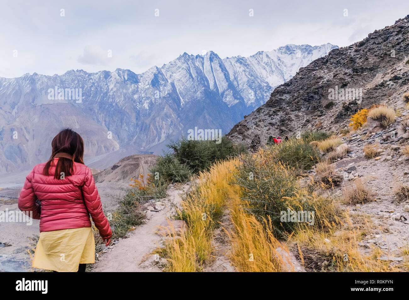 Tourists walking along the track at Passu glacier in autumn season, with snow capped mountains on the background. - Stock Image