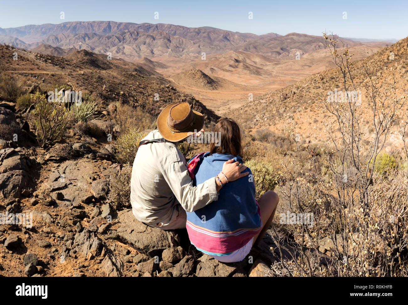 Couple sitting on top of a hill in the Richtersveld National Park - Stock Image