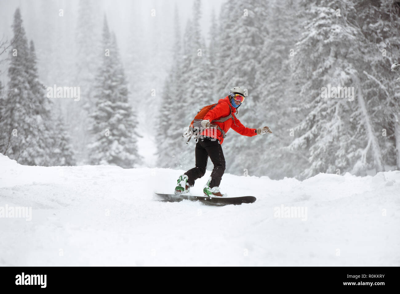 Snowboarder at offpiste slope in forest. Ski resort - Stock Image