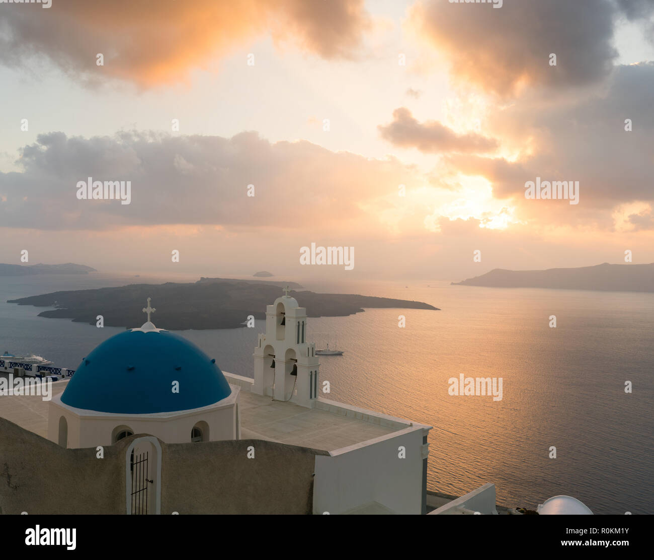 sunset over aegean sea with view to Virgin Mary Catholic Church Three Bells of Fira, Santorini. - Stock Image
