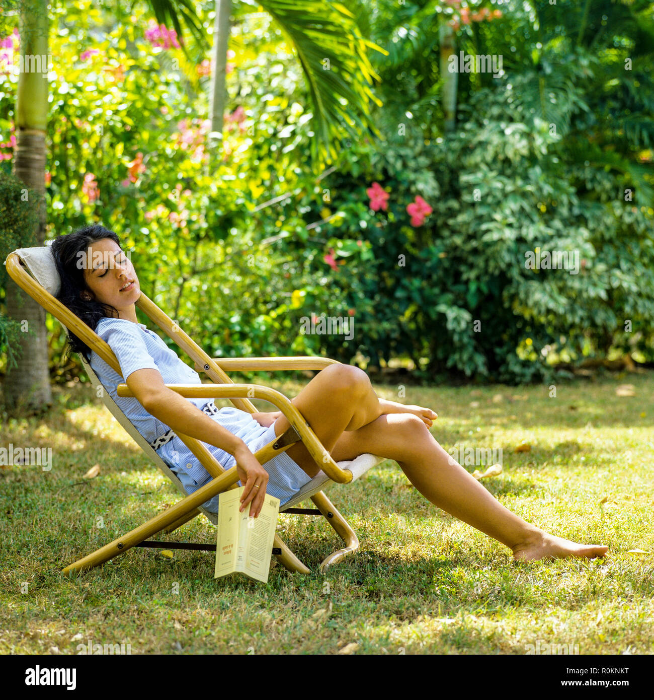 Young woman napping in deck chair, tropical garden, Guadeloupe, French West Indies, - Stock Image