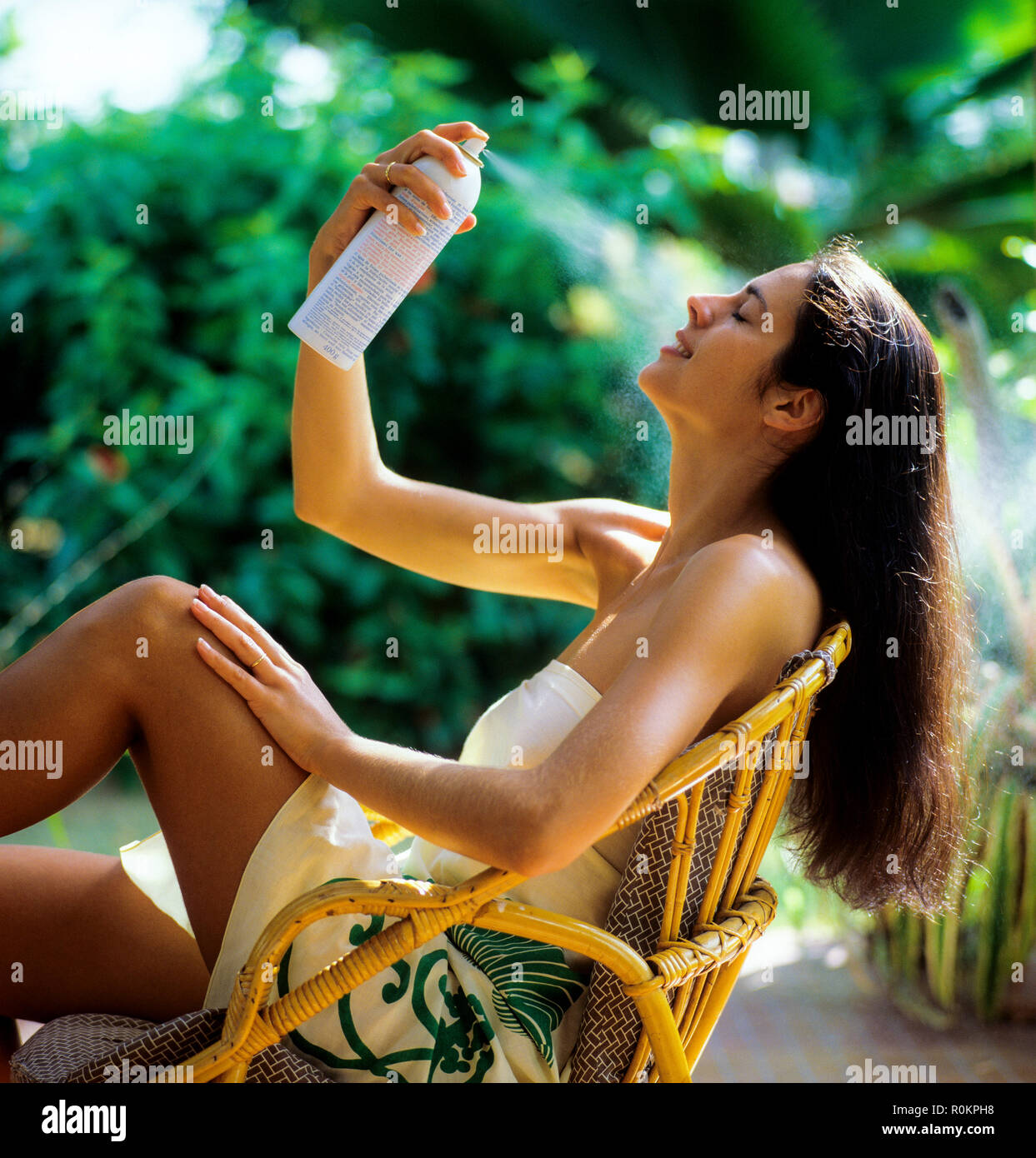 Young woman spraying her face with water atomizer, tropical garden, Guadeloupe, French West Indies, - Stock Image