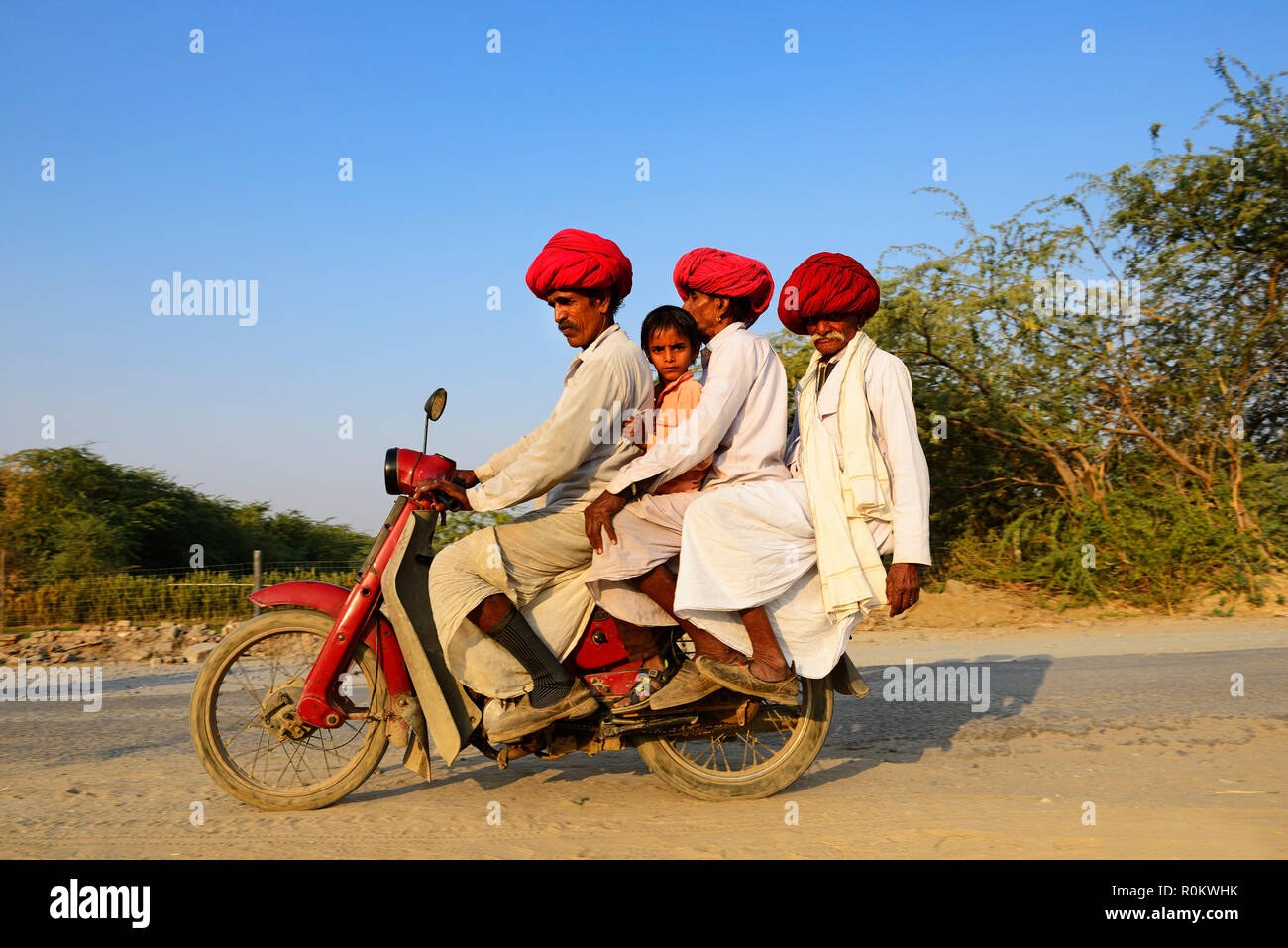 Four men from three generations riding together on a motorcycle, Rajasthan, India - Stock Image