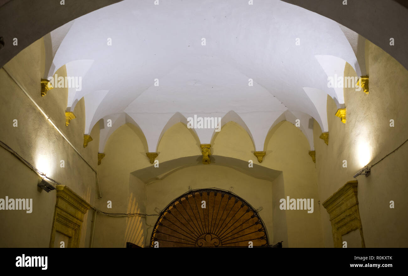 Close up of building with open courtyard and yellow walls in the town centre of Gallipoli, Puglia, Southern Italy. Stock Photo