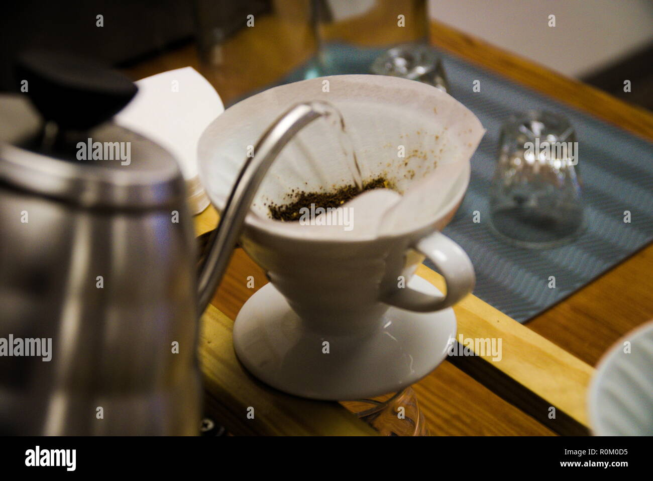 Water from a kettle is poured into a coffee filter in a mug with coffee grounds in it. The barista is making a pour over coffee. - Stock Image