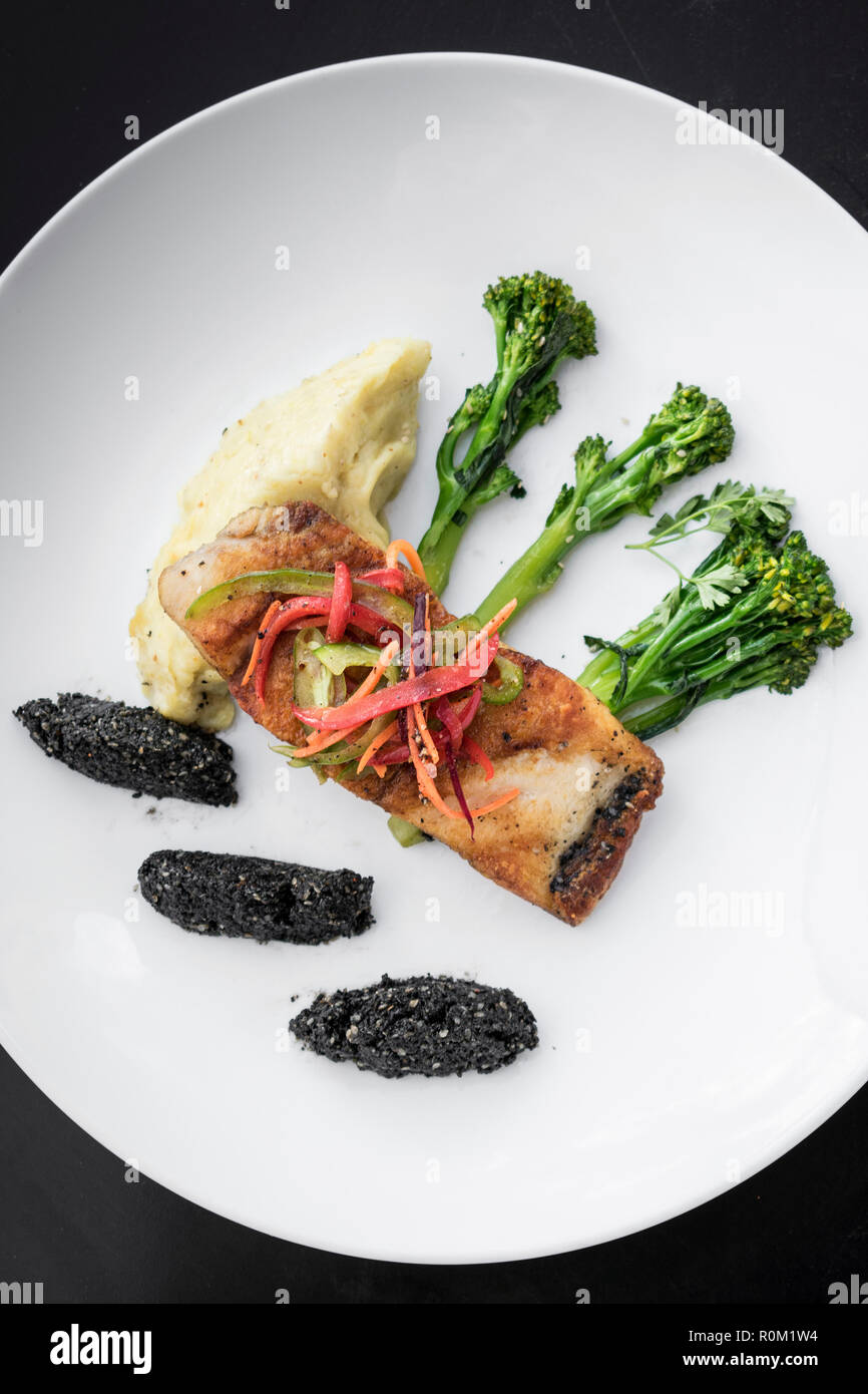 red snapper fish fillet with vegetables and black rice with black sesame seeds asian modern fusion dish in melbourne australia restaurant Stock Photo