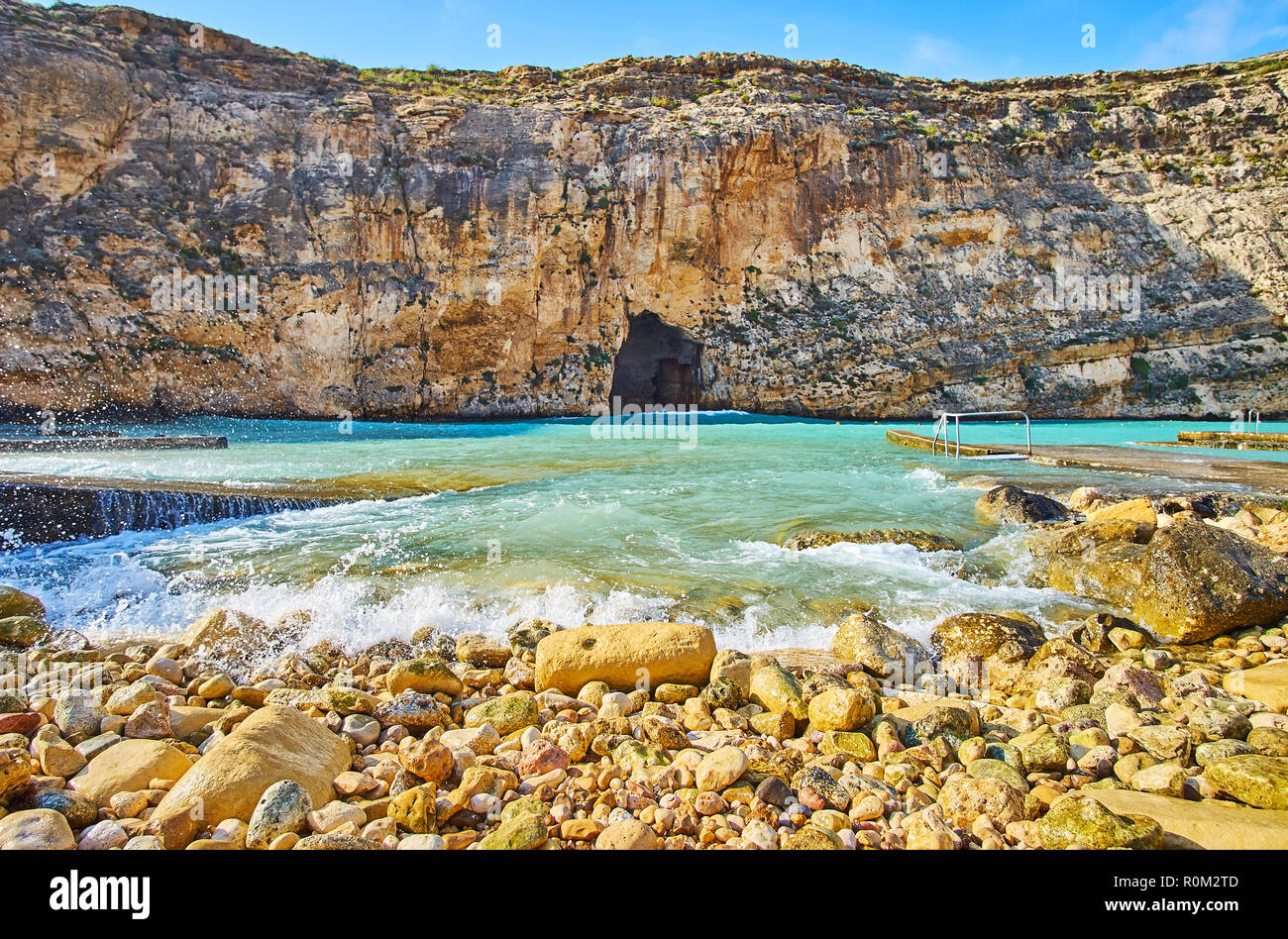 The Dwejra Inland Sea with tall cliffs, rocky shores, tiny beach and Blu Hole pass in rock, connecting this small lagoon with main sea waters, San Law - Stock Image