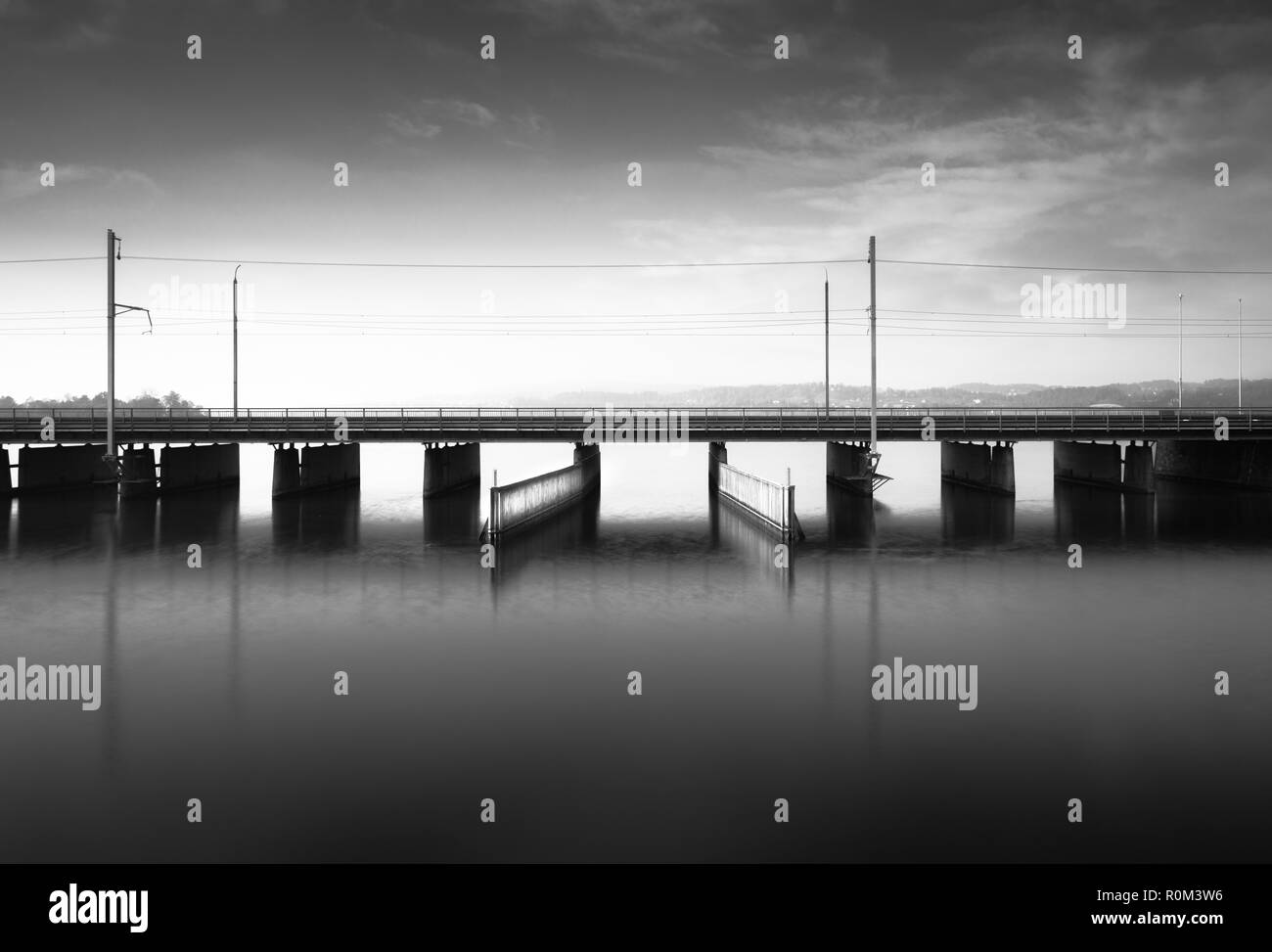 concrete bridge over water with a train line and road running parallel and a boat and ship passageway below - Stock Image
