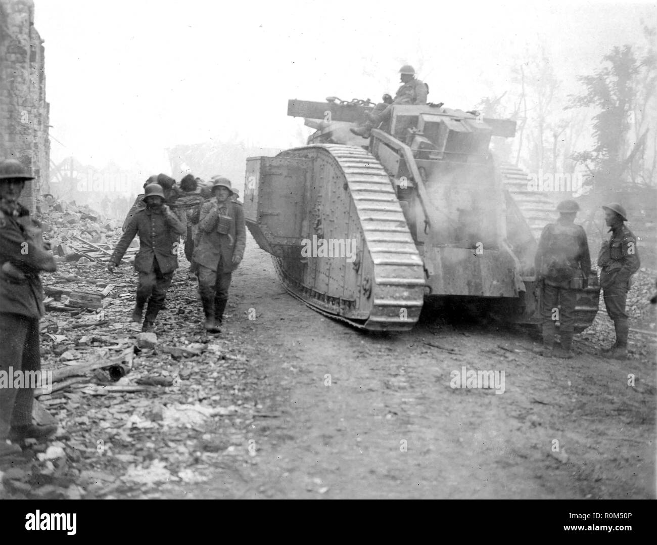 WW1: BATTLE OF AMIENS August 1918. Group of German prisoners carrying a stretcher pass a Canadian tank on the Amiens-Royde road - Stock Image