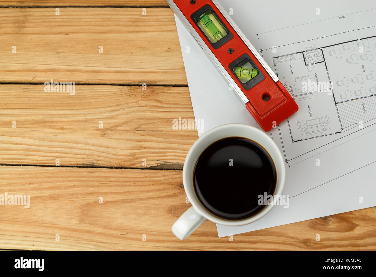 Cup of coffee with measurement tool and blueprint