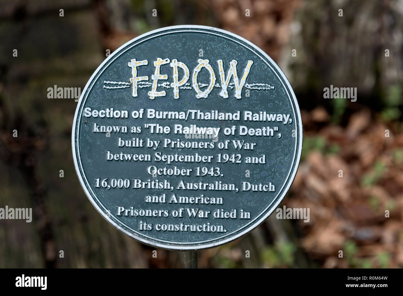A plaque of the FEPOW (Far East Prisoners of War) close to the short rail track, as part of a World War 11 memorial to allied prisoners of war, who di - Stock Image