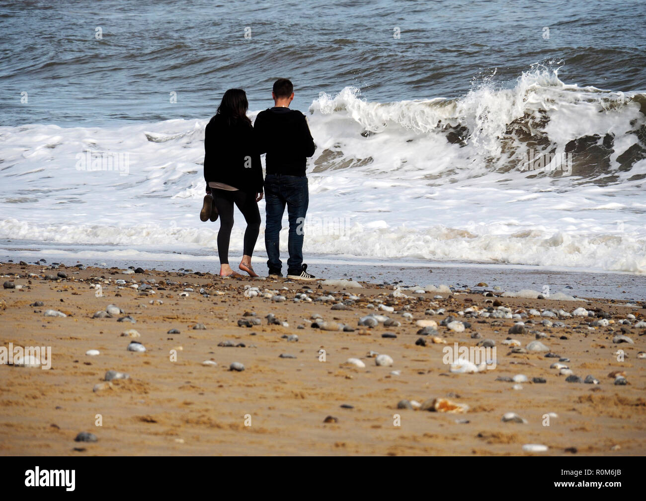 A young couple enjoy each other's company as they walk along a Norfolk beach trying to avoid the wash from the choppy sea's rashing waves. Stock Photo