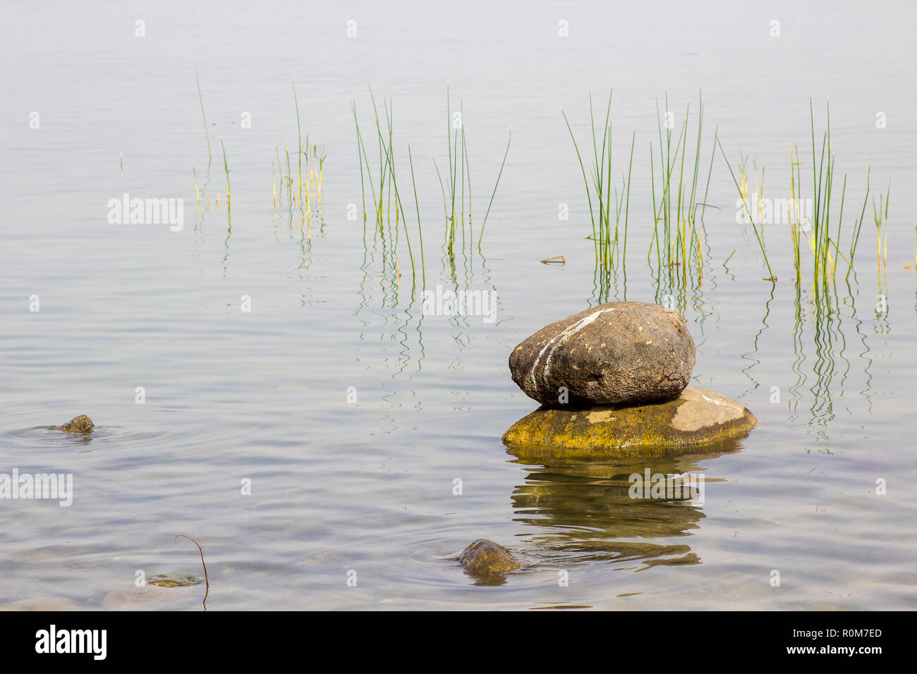 3 May 2018 Rocks piled together in flat calm shallows of the Sea Of Galilee Israel Israel on a hot hazy afternoon Stock Photo