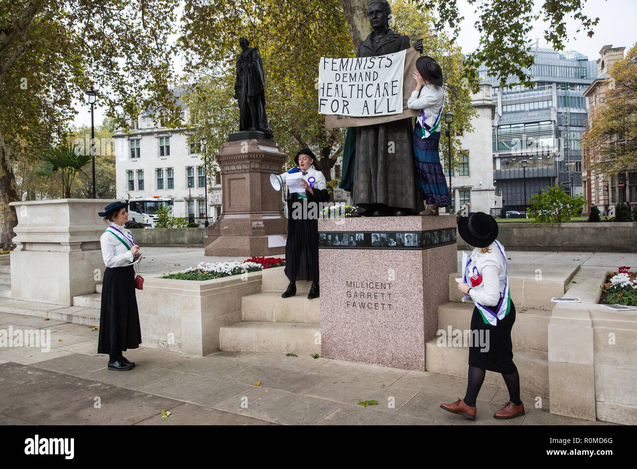 London, UK. 6th November, 2018. Activists from Feminist Fightback dressed as suffragettes change the sign on the new Millicent Fawcett statue in Parliament Square from 'Courage calls to Courage Everywhere' to 'Feminists demand healthcare for all' in protest against NHS charges for migrants. Under the new NHS charging system, migrants not considered 'settled' in the UK are being charged up to £7000 for pregnancy care and £1300 for an abortion in an NHS hospital. Credit: Mark Kerrison/Alamy Live News - Stock Image