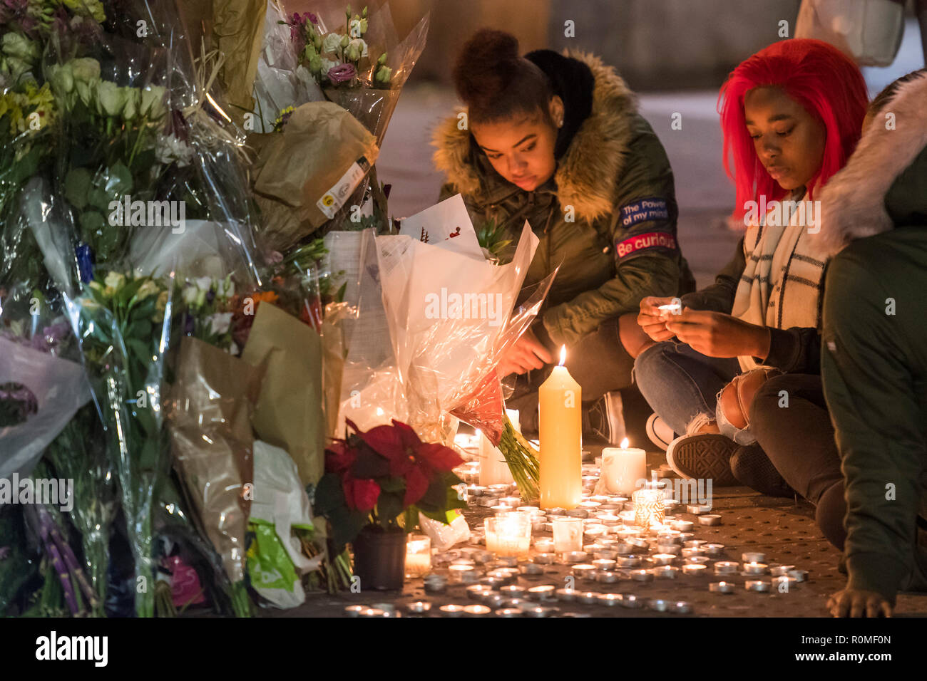 Clapham South, London, UK. 5th Nov 2018. After the crowd has gone a small group of girls stay to tend the candles - A vigil is held for Malcolm Mide-Madariola, 17, from Peckham, the victim of Friday's stabbning at Clapham South Tube Station. Credit: Guy Bell/Alamy Live News - Stock Image